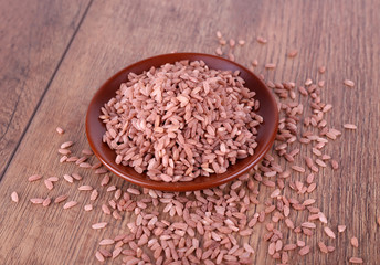 Red rice on plate on wooden background