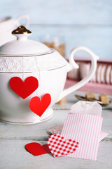 Heart shaped teabag tags, box and teapot on wooden background