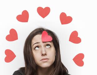 Sad girl looking at paper hearts