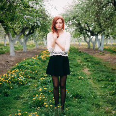 Portrait of young beautiful redhead woman in an apple garden