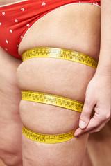 Fat woman measuring thigh leg tape measure