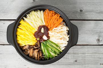 Korean cuisine, vegetarian Bibimbap in  a clay pot on a wooden t