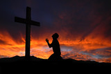 Fototapety Silhouette of man praying to a cross with heavenly cloudscape su