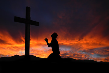 Silhouette of man praying to a cross with heavenly cloudscape su