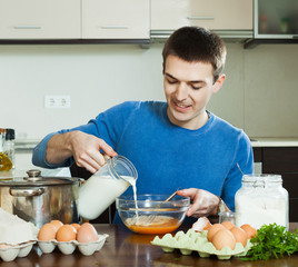 man pouring milk in bowl