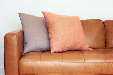 Close up of tan leather sofa with linen cushions