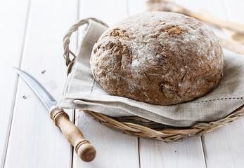 Freshly baked rye cob bread over white wooden background