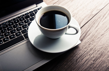 Cup of coffee and laptop on wooden table.
