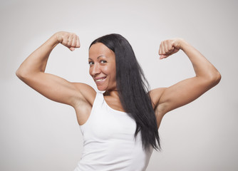 Young woman showing what her arm muscles