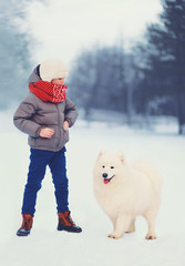 Winter and people concept - boy with white Samoyed dog outdoors