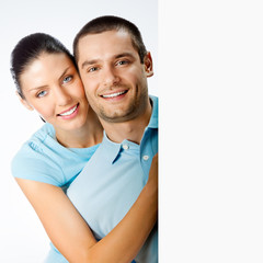 Cheerful young couple with signboard, on grey