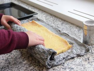Konditorin dreht Biskuitroulade ein