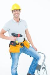Worker holding drill machine on step ladder