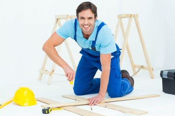 Happy repairman fixing screw on plank