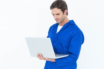 Mechanic using laptop over white background