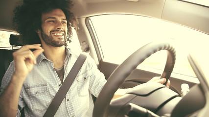 Happy man driving car retro look singing on music