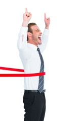 Happy businessman crossing the finish line and pointing up