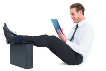 Businessman touching tablet with feet up on briefcase