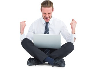 Businessman using laptop and cheering