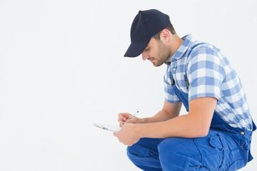 Handyman crouching while writing on clipboard