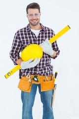 Handyman holding hard hat and spirit level