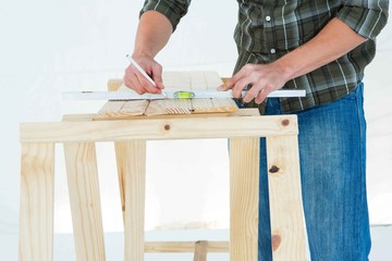 Worker using spirit level to mark on wooden plank