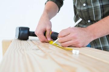 Carpenter using measure tape to mark on plank