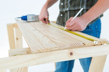 Carpenter marking with measure tape on wooden plank