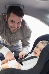Father securing baby in the car seat