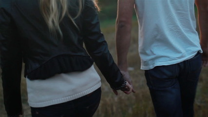 Young couple in love holding hands walking. Slow motion