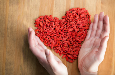 A female hands maiking a heart shape for goji berries