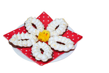 Easter meringue cookies on a white plate with a red napkin