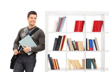 Male student leaning on a bookshelf