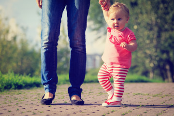 first steps of little girl in park