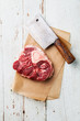 Raw fresh cross cut veal shank and meat cleaver for making Osso