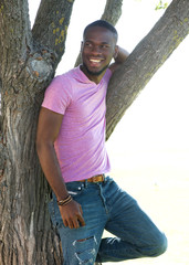 Cheerful young black man relaxing by tree