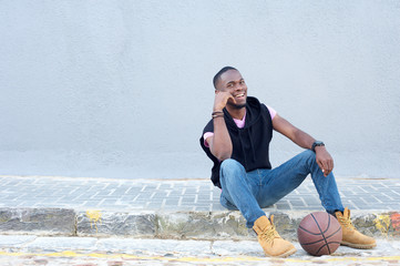 Happy young african american man sitting with basketball