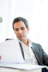 Young businessman sitting reading a report