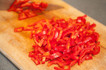 Closeup of sliced red sweet pepper on wooden board