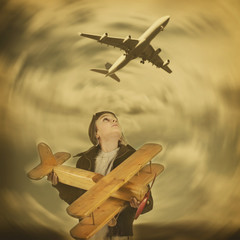 Junge mit Holzflugzeug sieht Passagierflugzeug