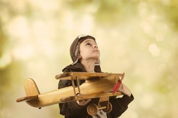 Kleiner Junge mit Holzflugzeug