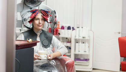 Young woman having a cup of coffee during hair colouring