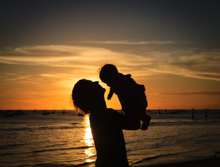 Father and little daughter silhouettes at sunset