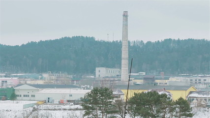 Winter view of old inactive factory not in use with smokestack