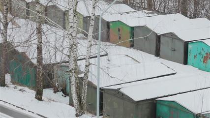 Rows of old school garages in winter. Pan