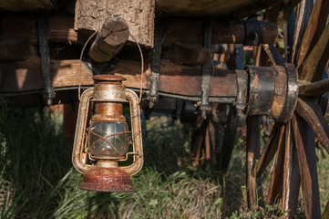 old rusty vintage oil lantern lamp hanging on a log