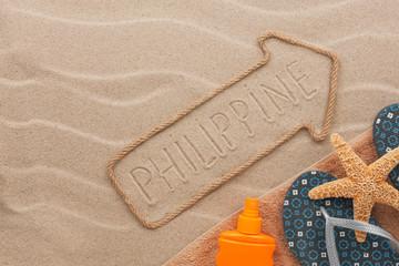 Philippines pointer and beach accessories lying on the sand
