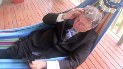 Businessman in a hammock working on his tablet.