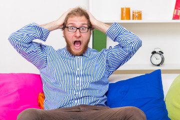 Shocked man screams in horror and sitting on the sofa