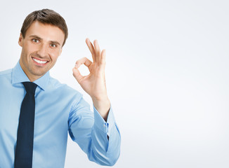 Businessman with okay gesture, on grey